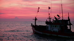 Thai fishing trawler moored with red sunset Stock Footage