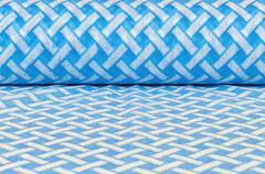 Rolled textile with blue and white pattern - stock photo