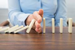 Close-up Of Businesswoman Stopping The Effect Of Domino With Hand At Desk Stock Photos