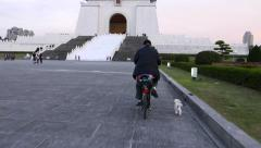 Man on bicycle with small dog at Zhongzheng memorial park Stock Footage