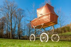 Retro style baby carriage outdoors on sunny day - stock photo