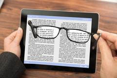 Close-up Of Person Reading E-book On Digital Tablet With Spectacles Kuvituskuvat