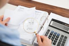 Close-up Of Businessperson Examining Receipts With Magnifying Glass Stock Photos
