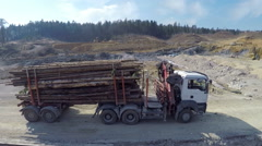 Stock Video Footage of Aerial view: Logs driving on dirty road