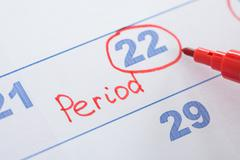 Close-up Of Sketchpen With Marked Menses Date On Calendar - stock photo