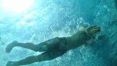 Slow motion as muscular Caucasian man swims underwater on surface of sea abov Stock Footage