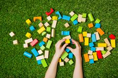 Stock Photo of Child hands constructing from color wooden blocks