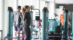 4K woman skipping in the gym with group of men using the machines in background Stock Footage