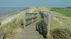 Coastal boardwalk path sand dunes sea blue sky Stock Footage