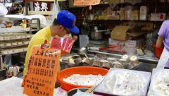 Young kitchener make traditional oriental cakes, indoor night sweets market Stock Footage