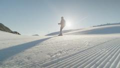 SLOW MOTION: Skier skiing on perfectly groomed snow in morning Stock Footage