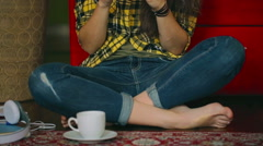 Girl sitting on the floor and texting on smartphone, steadycam shot Stock Footage