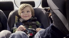 Closeup Of Little Boy Playing In His Car Seat, Excited To Go For A Drive - stock footage