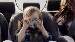 Little Boy Hides Behind His Toy Dinosaur And Smiles Happily In His Car Seat Stock Footage