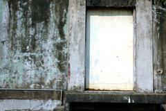 white rusty iron door with concrete wall - stock photo