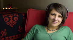 Attractive mature woman listen fast music with headphone at home  Stock Footage