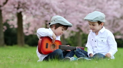Two adorable boys, sitting on the grass, playing guitar in a cherry garden - stock footage