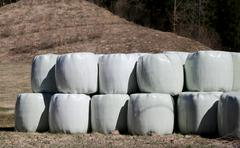 Hay bales wrapped in cellophane in farm field Stock Photos