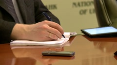 Close up shot of a persons hand writing something down at a meeting - stock footage