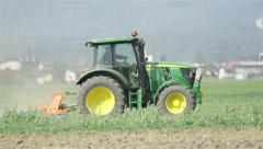 Tractor working on field in front of big city Stock Footage