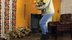 Woman with cap carry armful of wood and put near burning stove Stock Footage