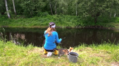 Blond woman fishing on pond shore with cute cat pet Stock Footage