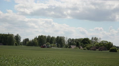 Tractor spray plant field near abandoned village with chemicals Stock Footage