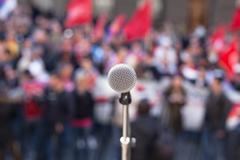 microphone in focus against unrecognizable crowd of people - stock photo