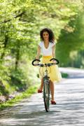 Young beautiful woman riding a bicycle in a park. Active people. Outdoors Kuvituskuvat