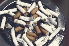 Bad addiction. Ashtray and cigarettes close-up Stock Photos
