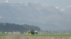 Farmer working on a big field with tractor Stock Footage