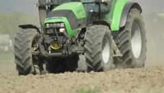 CLOSE UP: Tractor driving on a field in early spring Stock Footage