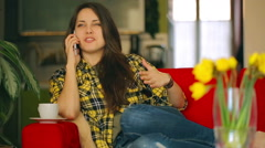 Girl talking on cellphone and smiling to the camera on red sofa Stock Footage