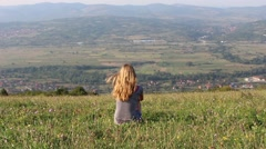 Girl Sitting on Top of the Hill Looking Far Away 1 - stock footage