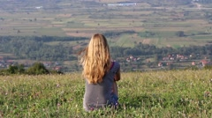 Girl Sitting on Top of the Hill Looking Far Away 2 Stock Footage