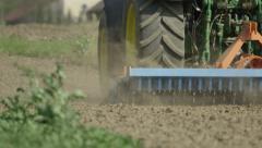 CLOSE UP SLOW MOTION: Farmer harrowing wheat field in spring Stock Footage
