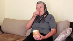 Grandmother Eating Popcorn from the Bag Stock Footage