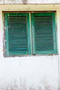 green wood windows with faded paint color - stock photo