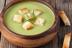 Healthy green cream broccoli soup with dried crusts in bowl Stock Photos