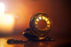 Vintage pocket watch near few lighting candles on dark background Stock Illustration