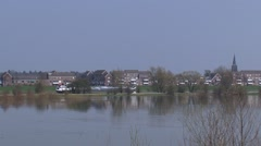 Inland cement ship upstream river IJssel behind lowered floodplains - long  shot Stock Footage
