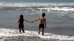 Couple Hesitating to Enter the Sea Stock Footage