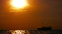 Stock Video Footage of Pirate Ship Tour Boat at Anchor off Patong Beach, Thailand, at sunset.
