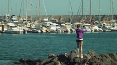 Long shot of blondie girl model shooting video photo on yacht club Stock Footage