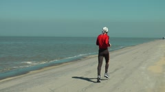 Runner beach sand sky sea red outfit movement Stock Footage