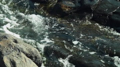 Ocean water floating through the vulcanic rocks close up Stock Footage