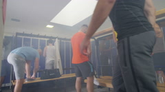 4K Cheerful sports players or gym buddies getting changed in men's locker room Stock Footage