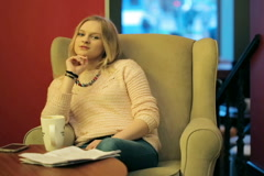 Girl sitting on armchair in the cafe and flirting to the camera Stock Footage