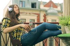Girl listening nostalgic music on the balcony Stock Footage
