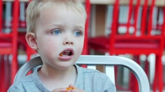 Young boy eating fast food at table Stock Footage